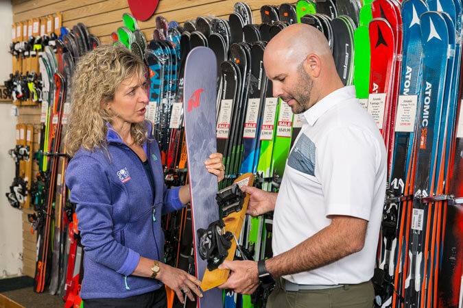 man and women looking closely at a ski in a retail store