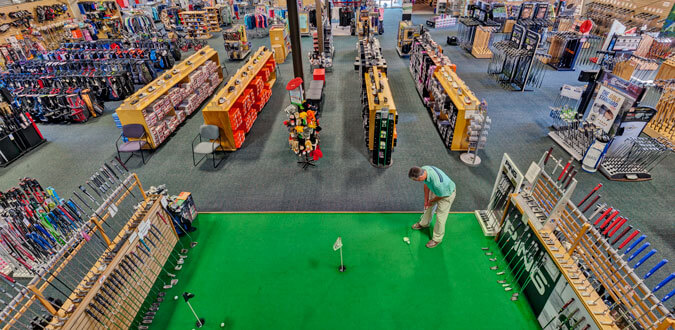 man putting on an indoor putting green inside a large retail store, view from above