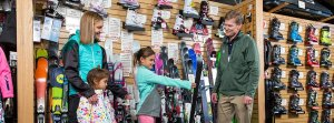 Girl holding a pair of skis with family behind her