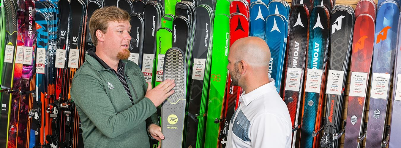 Store employee helping customer find the right pair of skis