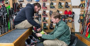 Employee helping to properly fit a gentleman in a ski boot