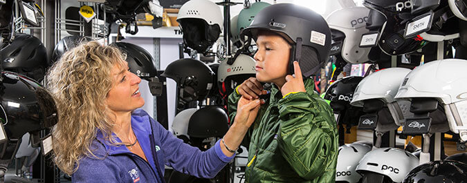 Employee helping young boy get fitted for a helmet in front of racks of different helmets