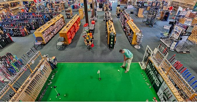 Retail floor with man putting on indoor putting green with tons of products in the background