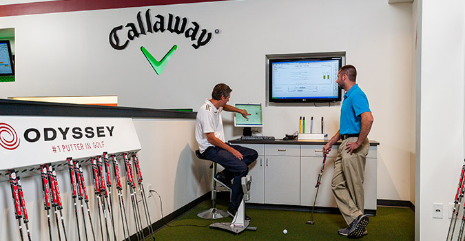 Two men looking at a computer screen reviewing the putters performance