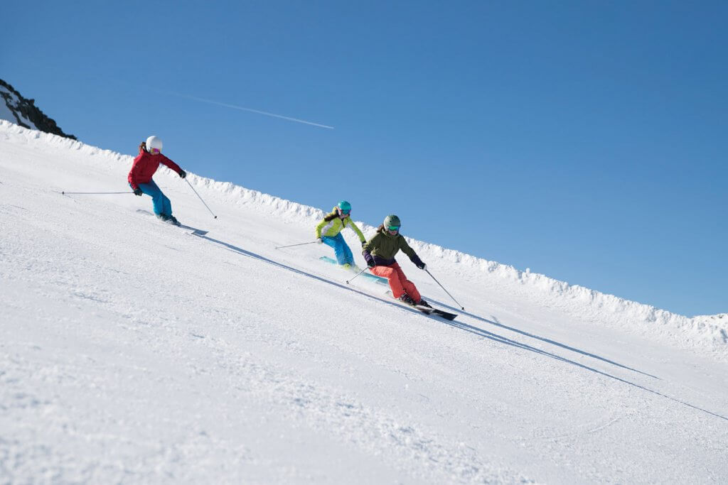 Three women skiing down a ski slope with a bright blue sky behind them
