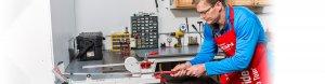 Employee re-gripping golf club in repair shop
