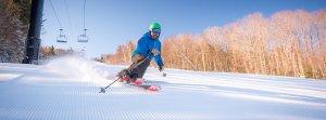 Man on a ski slope making turn on telemark skis