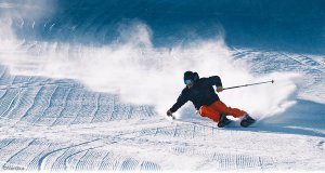 Man skiing down slope making a large carve with snow flying from the skis. The sun casting heavy shadows