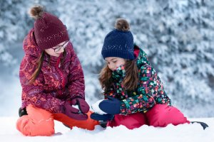 two girls dressed in bright winter outerwear playing in the snow