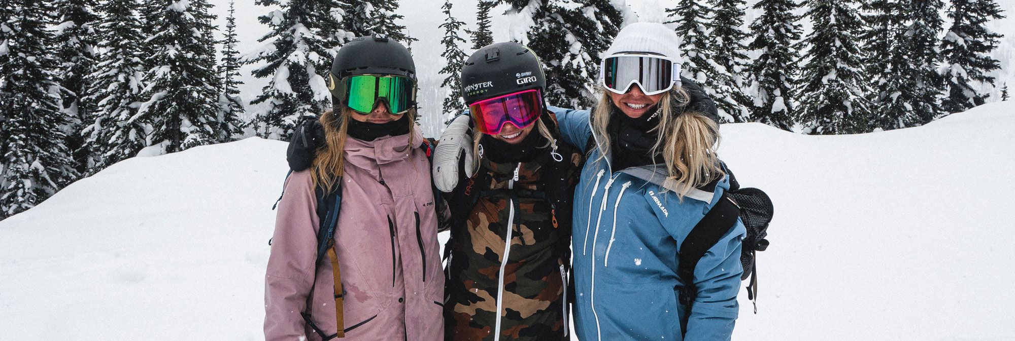 3 women in winter outdoor gear smiling in the snow